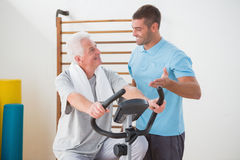 Senior man doing exercise bike with his trainer. Senior men doing exercise bike with his trainer in fitness studio Stock Image