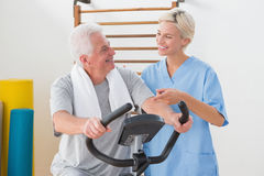 Senior man doing exercise bike with therapist Royalty Free Stock Photography