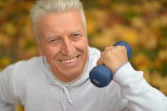 Senior man with dumbbell. Senior man doing exercises with dumbbell in autumnal park Royalty Free Stock Photography