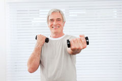 Senior man doing fitness training. With dumbbells at gym Royalty Free Stock Photo