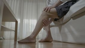 Senior man doing himself massage therapy on his tired legs relieve the pain and stress at home - stock video footage