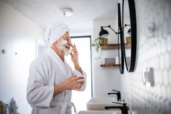 A senior man doing morning routine in bathroom indoors at home. Copy space. A senior man doing morning routine in bathroom indoors at home, looking in mirror royalty free stock photography