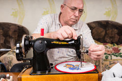 Senior Man Doing Needlepoint on Sewing Machine