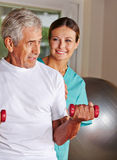 Senior man doing rehab sports. Senior men doing rehab sports in nursing home with a physiotherapist Royalty Free Stock Photo