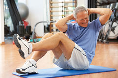 Senior Man Doing Sit Ups. In Gym Stock Photo