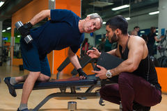 Senior man doing weight exercise with trainer. Senior caucasian men doing weight exercise with personal trainer. Male adult exercising with assistance of royalty free stock photography