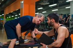 Senior man doing weight exercise with trainer. Senior caucasian men doing weight exercise with personal trainer. Male adult exercising with assistance of stock photos