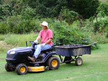 Senior Man doing Yard Work. Middle-aged man with lawnmower pulling a wagon Royalty Free Stock Photo
