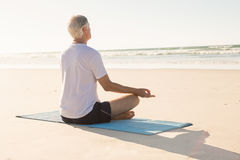 Senior man doing yoga at beach Stock Photos