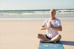 Senior man doing yoga while sitting at beach Stock Image