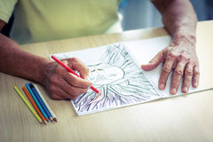 Senior man drawing with a colored pencil in drawing book. At home royalty free illustration