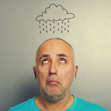 Senior man with drawing storm cloud Stock Photography