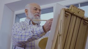 Senior man draws picture on easel standing near the window