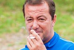 Senior man dressed in formal clothes smoking cigaretes Royalty Free Stock Photos