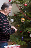 Senior man dressing Christmas tree Stock Image