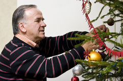 Senior man dressing Christmas tree Royalty Free Stock Photos