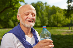 Senior man drinking bottle of water in summer. Thirsty senior man drinking a bottle of water in summer stock image