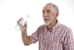 Senior man drinking bottled water. Senior man about to drink from water bottle. Isolated on white. All logos removed Stock Photo