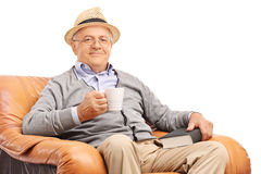 Senior man drinking coffee seated in an armchair Royalty Free Stock Images