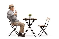 Senior man drinking coffee at a table stock photo