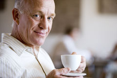 Senior man drinking cup of coffee in caf�, smiling, close-up, side view, portrait Stock Images