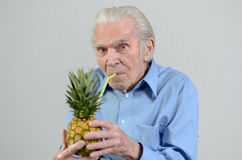Senior man drinking fresh pineapple juice Stock Photos