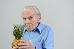 Senior man drinking fresh pineapple juice Royalty Free Stock Photo