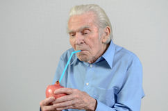 Senior man drinking fresh pomegranate juice Royalty Free Stock Photos