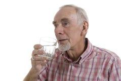 Senior man drinking glass of water. Senior man enjoying a healthful glass of water. White background Royalty Free Stock Image