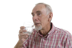 Senior man drinking a glass of water. Healthy senior man drinking a glass of water. White background royalty free stock image