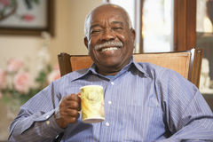 Senior man drinking hot beverage royalty free stock photos