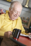 Senior man drinking hot beverage Royalty Free Stock Images