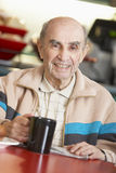 Senior man drinking hot beverage Stock Image