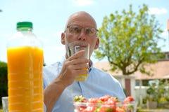 Senior man drinking  orange juice in her garden Stock Photo