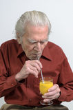 Senior man drinking orange juice. Portrait with copy space on gray Royalty Free Stock Photo