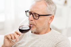 Senior man drinking red wine from glass at home. People, alcohol and drinks concept - senior man drinking red wine from glass at home Stock Photo