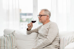 Senior man drinking red wine from glass at home. People, alcohol and drinks concept - senior man drinking red wine from glass at home Royalty Free Stock Images