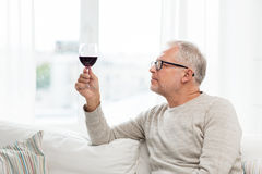 Senior man drinking red wine from glass at home. People, alcohol and drinks concept - senior man drinking red wine from glass at home Stock Photography