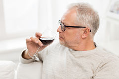 Senior man drinking red wine from glass at home. People, alcohol and drinks concept - senior man drinking red wine from glass at home Royalty Free Stock Photography