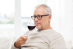 Senior man drinking red wine from glass at home. People, alcohol and drinks concept - senior man drinking red wine from glass at home Stock Photos