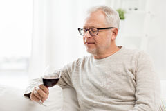 Senior man drinking red wine from glass at home Stock Photos