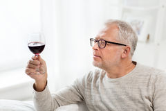 Senior man drinking red wine from glass at home. People, alcohol and drinks concept - senior man drinking red wine from glass at home Stock Image