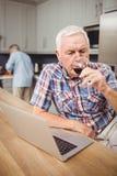 Senior man drinking red wine while using laptop Royalty Free Stock Photos