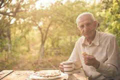 Senior man drinking a tea. At the garden Stock Image