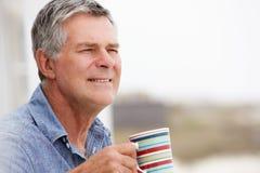 Senior man drinking tea outdoors Royalty Free Stock Photos