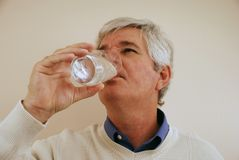 Senior Man Drinking Water. Handsome baby-boomer gentleman drinking water from a glass Royalty Free Stock Images