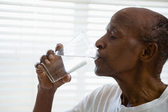 Senior man drinking water against window in bathroom. At home Stock Image