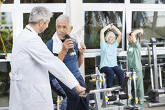 Senior Man Drinking Water By Doctor In Fitness Studio Stock Photography