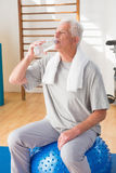 Senior man drinking water. In fitness studio Royalty Free Stock Photography