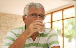 Senior man drinking water. Senior man drinking water at home and looking at camera Royalty Free Stock Images